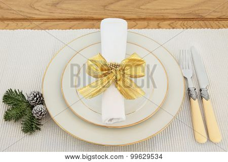 Elegant christmas dinner place setting with plates, antique cutlery, napkin and gold bow over silver table runner and oak.