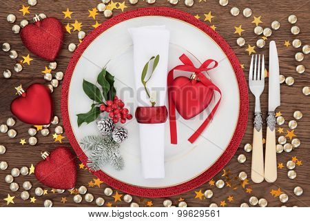 Christmas dinner place setting with plate, napkin, cutlery, holly and mistletoe with baubles over oak table background.