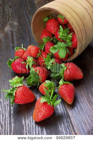 Strawberries in wood bowl on a wood background