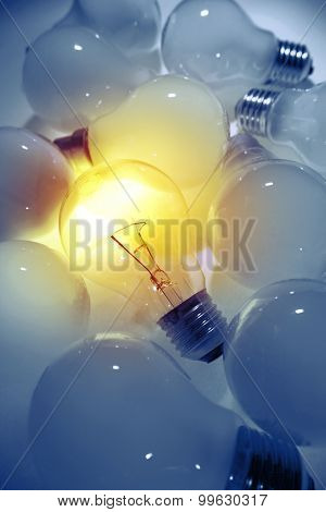 One bright bulb in line of dull light bulbs. Standing out concept
