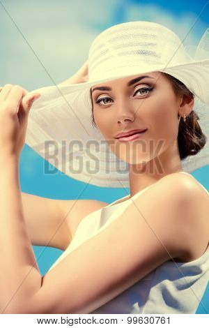 Portrait of a beautiful smiling woman in light white dress and elegant hat over blue sky. Beauty, fashion. Summer vacation.