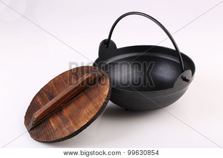 Black Iron Pot With Wooden Lid  Isolated On White Background