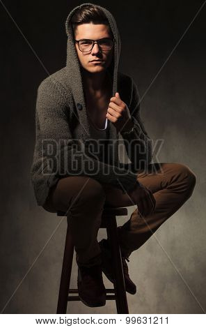 Casual young man sitting on a stool while fixing his sweater.