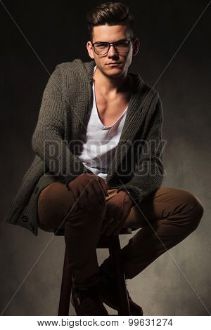 Handsome casual man holding one hand on his knee while sitting on a stool.