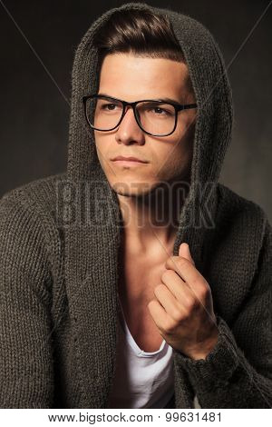 Pensive young man looking away while wearing a grey hoodie.