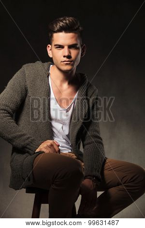Fashion man wearing a white shirt and a grey sweater sitting on a chair while looking at the camera.