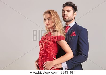 Side view of a young elegant couple standing embraced while looking away.