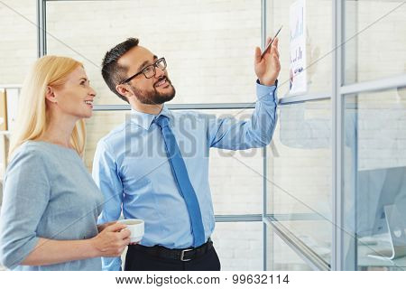 Young businessman showing his plan to CEO