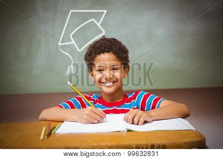 Graduation hat vector against little boy writing book in classroom