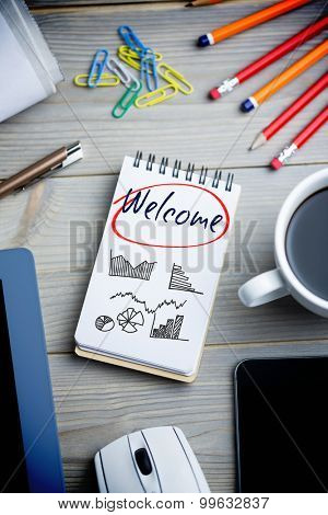 The word welcome and business graphs against notepad on desk