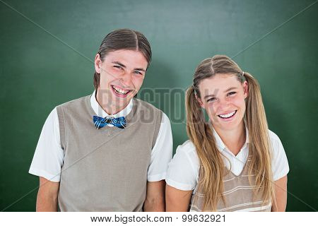 Smiling geeky hipsters looking at camera against green chalkboard