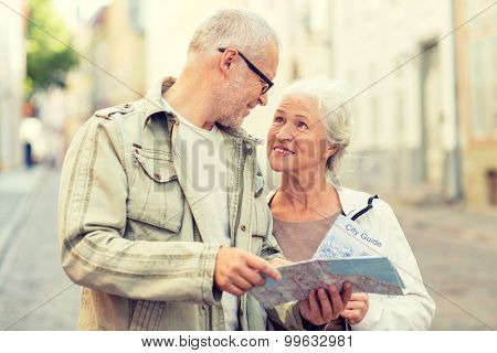 family, age, tourism, travel and people concept - senior couple with map and city guide on street