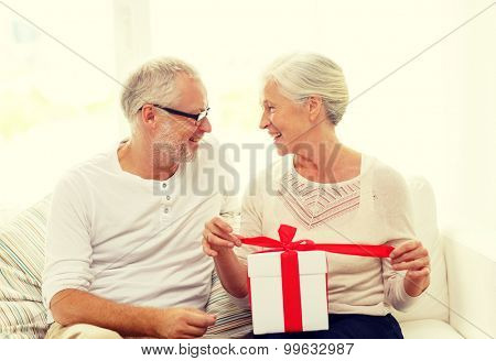 family, holidays, christmas, age and people concept - happy senior couple with gift box at home