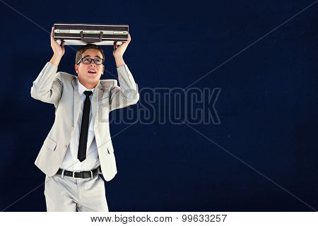 Handsome businessman sheltering with briefcase against navy blue