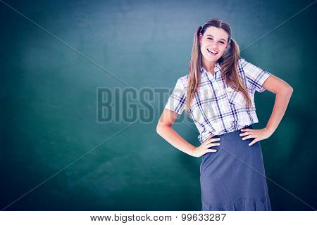 Geeky hipster with hands on hips against green chalkboard