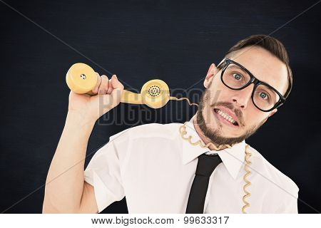 Geeky businessman being strangled by phone cord against blackboard
