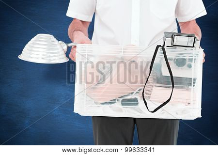 Businessman holding box of his things against blue chalkboard