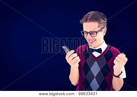 Excited geeky hipster texting on the phone against navy blue
