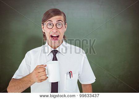 Geeky businessman holding a mug against green chalkboard