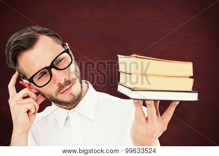 Geeky young man looking at pile of books against desk