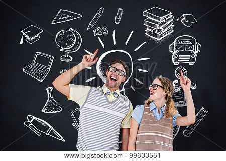 Happy geeky hipster couple pointing up against blackboard