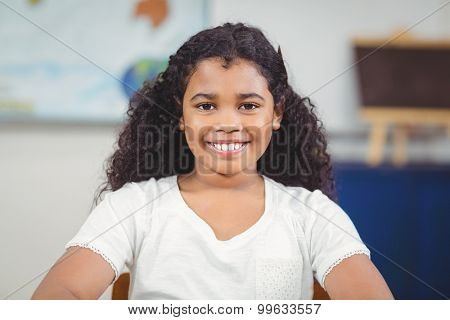Portrait of smiling pupil sitting in a classroom in school