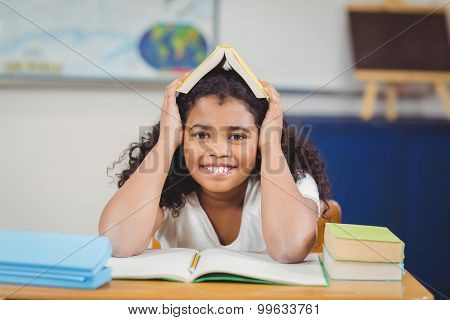 Portrait of smiling pupil holding book on head in a classroom in school