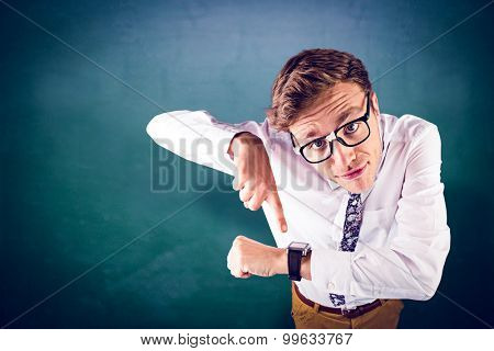 Geeky businessman pointing to watch against green chalkboard