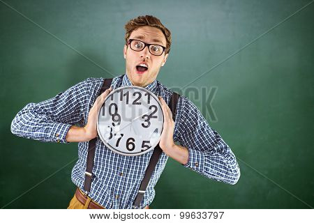 Geeky businessman holding a clock against green chalkboard
