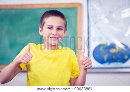 Portrait of smiling pupil doing thumbs up in a classroom in school