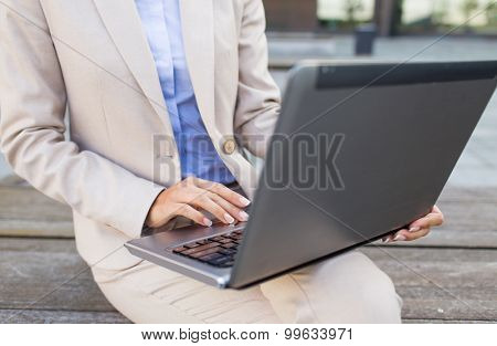 business, technology and people concept - close up of smiling woman with laptop computer sitting on bench in city