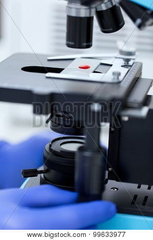 science, chemistry, biology, medicine and people concept - close up of scientist hands with microscope and blood test sample making research in clinical laboratory