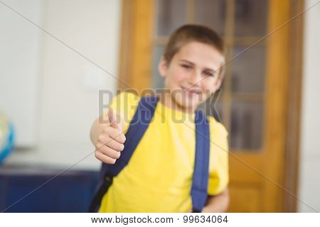 Portrait of smiling pupil with schoolbag doing thumbs up in a classroom in school