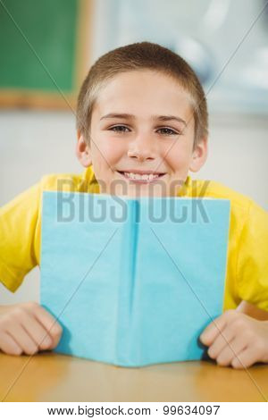 Portrait of smiling pupil reading book in a classroom in school