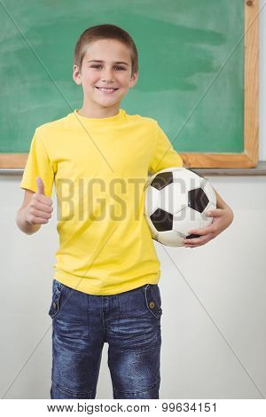 Portrait of smiling pupil holding football in a classroom in school