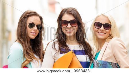 holidays, tourism and happy people concept - three smiling women in sunglasses with bags in the city