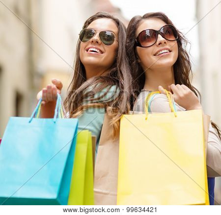 shopping, sale, happy people and tourism concept - two smiling girls in sunglasses with shopping bags in ctiy