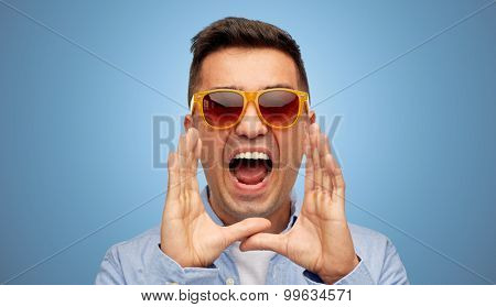 summer, emotions, communication and people concept - face of angry middle aged latin man in shirt and sunglasses shouting over blue background