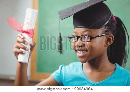 Smiling pupil with mortar board and diploma in a classroom