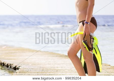 Young Woman Holding Snorkeling Gear Looking At The Sea