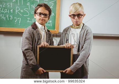 Portrait of pupils dressed up as teachers holding chalkboard in a classroom