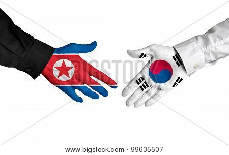 North Korea and South Korea leaders shaking hands on a deal agreement