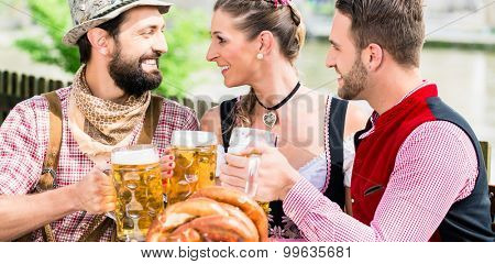 People with beer and pretzel in Bavarian inn eating and drinking