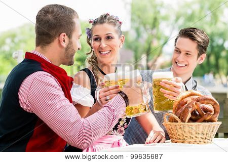 Friends in beer garden clinking glasses with beer, pretzel standing on the table