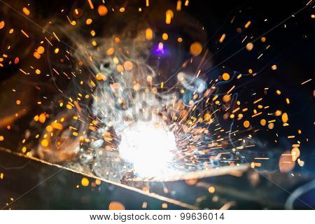 Close-up of welder working in workshop. Low depth of focus