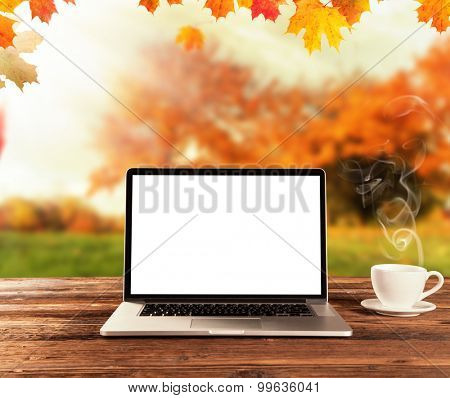 Laptop placed on a wooden table with autumn landscape as background