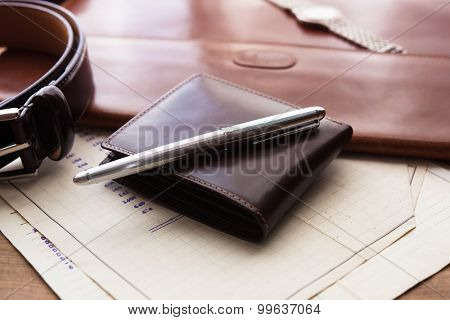 Documents, pen, belt and a wallet on a wooden desk. hotel table or gentleman's desk. shallow depth of field.