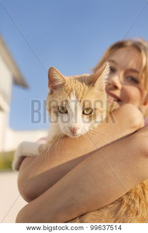 Beautiful blond young woman with ginger cat
