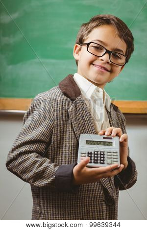 Portrait of pupil dressed up as teacher showing calculator in a classroom