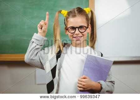 Portrait of cute pupil holding books in a classroom in school